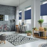 Soft lit room with a desk, a bike, and Veneta™ Top-Down/Bottom-Up cellular shades in blue
